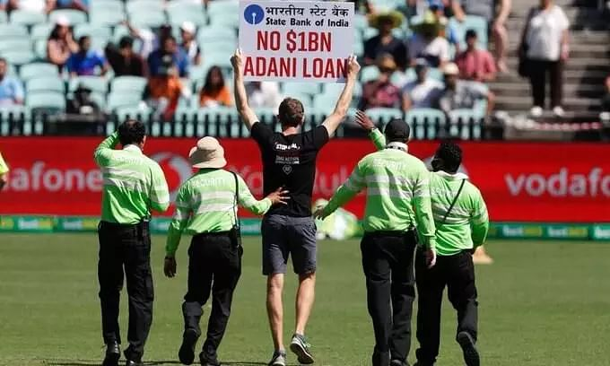 'Stop Adani' protestors barge into ground holding placards
